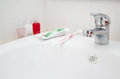 Faucet, toothpaste, toothbrush and bath accessories Royalty Free Stock Photo