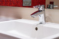 Faucet on white sink Royalty Free Stock Image