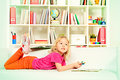 Favorite activity cute little girl lying on a sofa at home and drawing Royalty Free Stock Photo