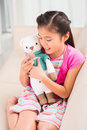 Favorite toy little girl playing with her knitted sitting on sofa Stock Photography