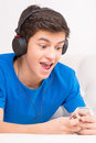 Favourite music cheerful teenage boy in headphones listening to the and smiling Royalty Free Stock Photography