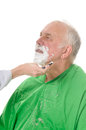 Feamale barber shaving client elderly man getting a shave from a female Royalty Free Stock Photo