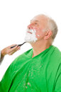 Feamale barber shaving client elderly man getting a shave from a female Stock Photos