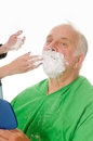 Feamale barber shaving client elderly man getting a shave from a female Stock Images