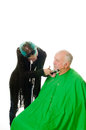 Feamale barber shaving client elderly men getting a shave from a female Stock Image