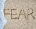 Fear word hand written with wave foam on sand beach white background Royalty Free Stock Image