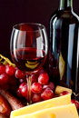 Feast wine cheese sausage and grapes at a Stock Image