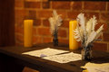 Feather quill pens candle and old paper on wooden desk. Vintage. Royalty Free Stock Photo