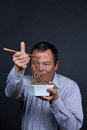 Fed up with chopsticks guy getting pretty his attempts on eating Stock Photos