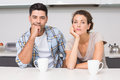 Fed up couple having coffee looking at camera home in kitchen Royalty Free Stock Photo