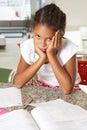 Fed up girl doing homework in der küche Lizenzfreie Stockfotos