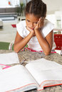 Fed up girl doing homework in kitchen Stock Images