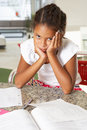 Fed up girl doing homework na cozinha Fotos de Stock Royalty Free