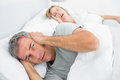 Fed up man blocking his ears from noise of wife snoring men at home in bedroom Royalty Free Stock Images