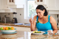 Fed Up Overweight Woman Eating Healthy Meal in Kitchen
