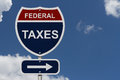 Federal taxes this way blue and red interstate sign with word and an arrow with sky background Stock Image
