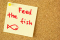 Feed the fish remind sticker on cork colorful yellow pined corkboard Royalty Free Stock Photos