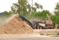 Feeding chipper salvaging wood garbage wood chips to be used as fuel lumber mill Royalty Free Stock Images