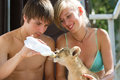 Feeding little lion cub with milk photo set of people taking care of month old male Stock Photo