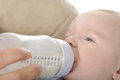 Feeding mother her baby with a milk bottle Stock Photos