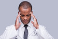 Feeling awful headache depressed african doctor touching his head with hands and keeping eyes closed while standing against grey Royalty Free Stock Photography