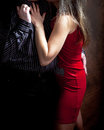 Feeling of closeness and love affection tenderness young woman red dress man holding her tenderly shooting in the pavilion dark Stock Photography