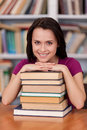 Feeling confident before her final exams. Cheerful young female student holding books and smiling while standing at the library Stock Images