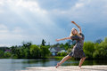 Feeling free: portrait of young beautiful blond lady dancing girl with falling sun lighting rays from blue sky at water lake Royalty Free Stock Photo