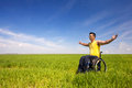 Feeling of freedom happy handicapped man on a wheelchair with wide outstretched arms over a green meadow Royalty Free Stock Photography