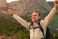 Feeling freedom man on the mountain landscape happy with victory gesture hands view Stock Image
