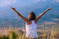 Feeling freedom young woman yong sitting on the mountain steep Royalty Free Stock Photography