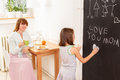 Feeling loved mother in the kitchen looking at her daughter who wites on chalkboard Stock Photography