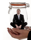 Feeling trapped a businessman sitting inside a glass jar as business concept for in the workplace Stock Photography