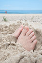 Feet on beach buried in sand with uncovered toes a Stock Photos