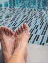 Feet on the cement floor beside the pool. Royalty Free Stock Photo