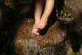 Feet of child dipped in cold water in a stream compequena waterfall in a park playground wet in japan square in curitiba paraná Stock Photos
