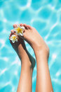 Feet dangling over swimming pool with flowers Royalty Free Stock Photo