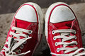 Feet in dirty red sneakers and jeans outdoors. Royalty Free Stock Photo