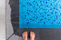 Feet on the edge of the swimming pool Royalty Free Stock Photo