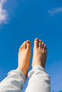 Feet female against blue sky Royalty Free Stock Images