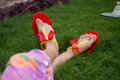 Only feet of a girl wearing red slippers and sitting in grass Royalty Free Stock Photo