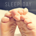 The feet of a man in bed and text sleep day