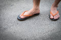 Feet of a man wearing sandals on concrete floor. Royalty Free Stock Photo