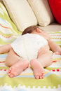 Feet of newborn baby boy seven weeks age sleeping on couch Stock Image