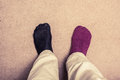 Feet with odd socks on carpet one black and one purple Stock Photo