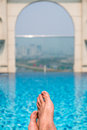 Feet over the sparkling pool on top of building with Saigon aeri Royalty Free Stock Photo