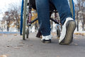 Feet of a person pushing a wheelchair low angle close up view the along tarred street Stock Photos