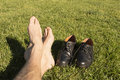 Feet relaxing in the grass with his shoes Royalty Free Stock Photos