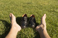 Feet relaxing in the grass with his shoes Royalty Free Stock Photography