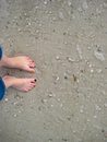 Feet in sand on a rocky beach Royalty Free Stock Photo